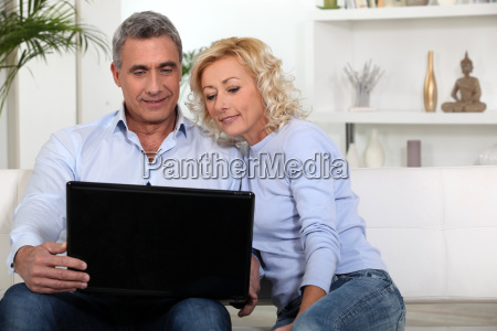 couple sitting on sofa looking at