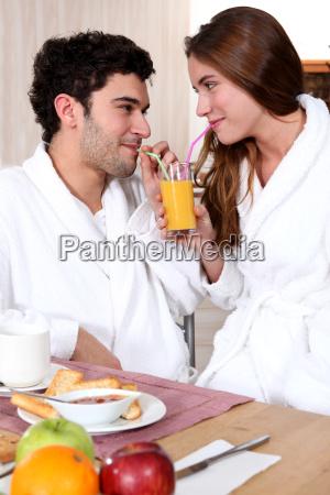 young couple in bathrobe drinking orange