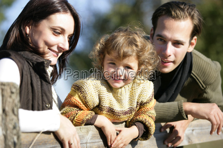 young family leaning against fence
