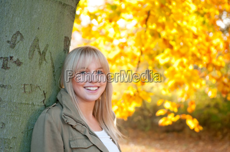 young woman standing at a tree