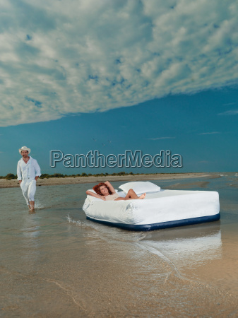 young couple laying bed floating on