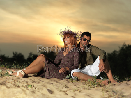 young couple sitting in the sand