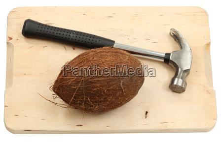 kokosnussfrucht und ein hammer isoliert ueber