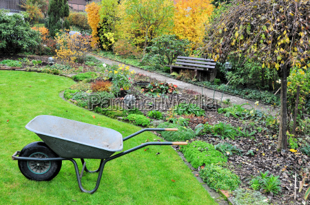 beautiful garden in autumn with wheelbarrow