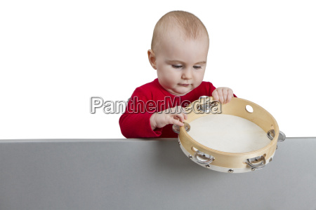 young child holding tambourine behind gray