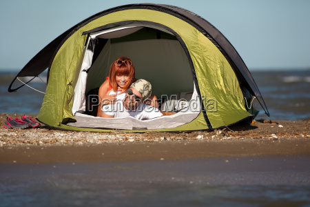 happy young couple sitting in tent