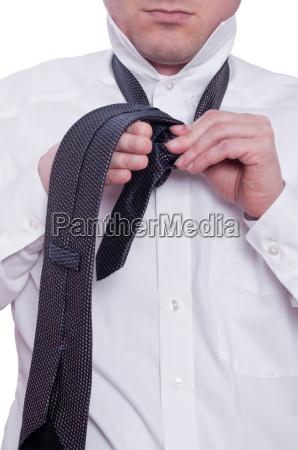 man ties necktie