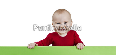 young child holding green sign