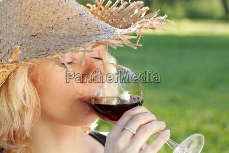 junge frau mit sonnenhut beim rotwein