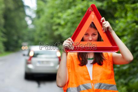 junge weibliche fahrer eine autopanne mit