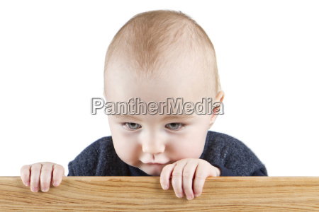 young child holding wooden board