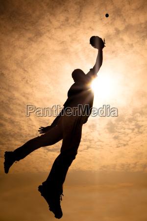 das schattenbild des baseball spielers springend