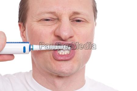 mannt mit elektrischer zahnbuerste tut zaehne
