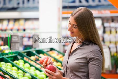 woman in supermarket buying fruit