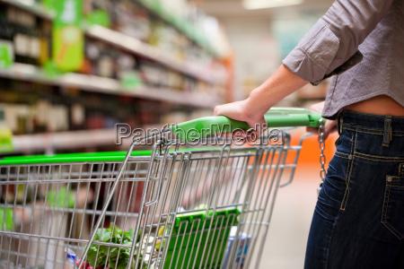 young woman pushing shopping cart in