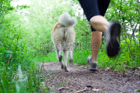 woman running cross country with dog