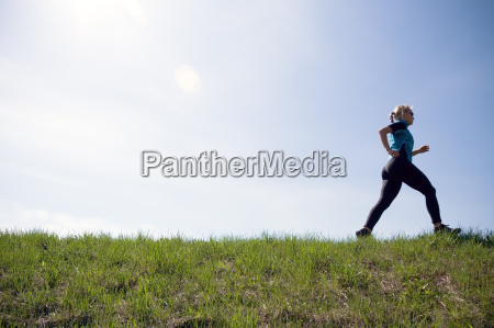 young woman running outdoors on green