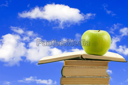 books with apple on sky background