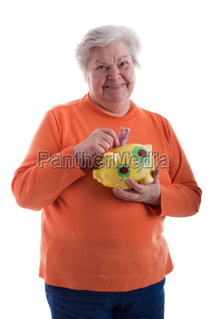pensioner holding piggy bank and smiling