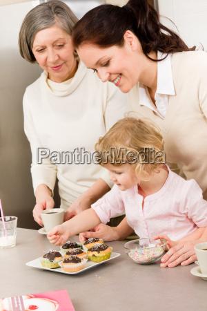 tochter und mutter schmuecken kleine kuchen