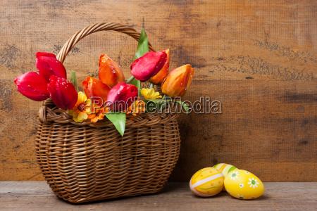 koerbchen mit seidenblumen neben ostereiern