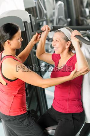 persoenlicher trainer unterstuetzen aeltere frau im