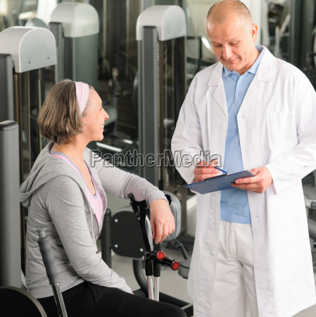 physiotherapeut unterstuetzt aktive seniorin im fitnessstudio