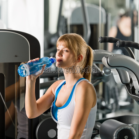 woman drink water at fitness machine