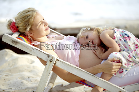 junge schwangere mutter sitzt mit ihrer