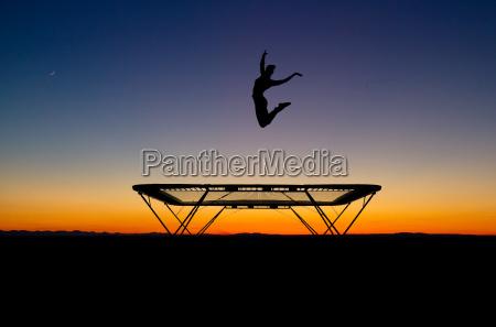 silhouette einer turnerin auf dem trampolin