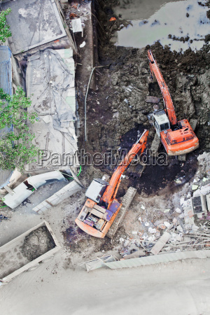 two diggers moving soil in unision