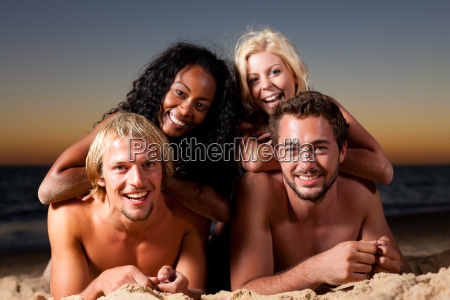 four friends on the beach at