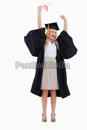 blonde studentin in graduierten robe haelt
