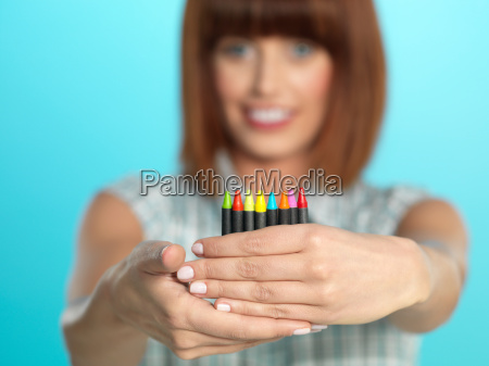 attractive young woman holding colorful crayons