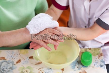 altenpflegerin waescht patientin die haende