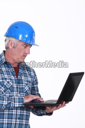 mature craftsman working on his laptop