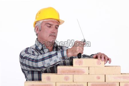 a mature mason building a wall