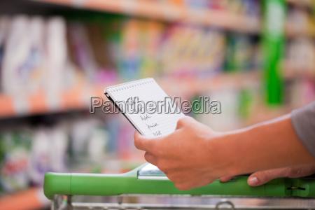 junge frau schiebt einkaufswagen in supermarkt