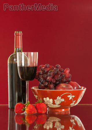 rotweinflasche und obst mit glas