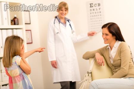 girl reading eye chart pediatrician office