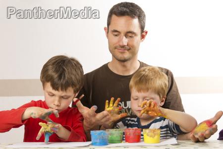vater malt mit seinen kindern mit