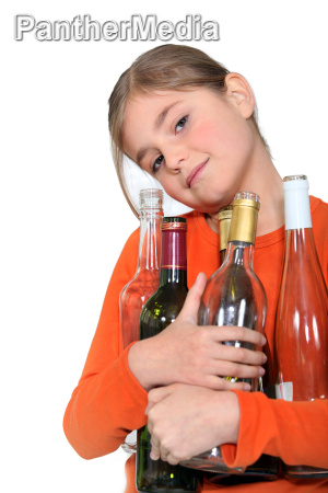 young girl holding empty wine bottles