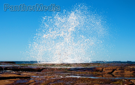 big splash waves hitting rocks