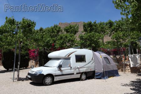 wohnmobil mit zelt auf einem campingplatz