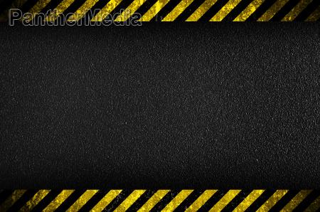 dunkler hintergrund mit vorsicht gelben streifen