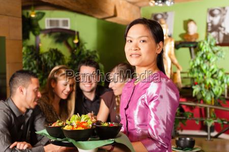 junge leute mit bedienung essen in