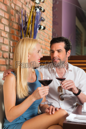 attractive couple drinking red wine at