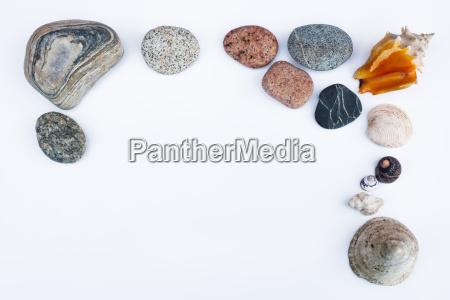dekorativer rahmen aus kieselsteinen und muscheln
