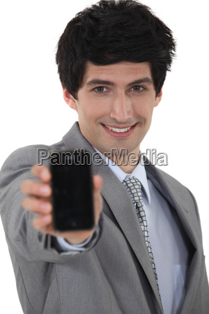 smiling businessman holding up his mobile