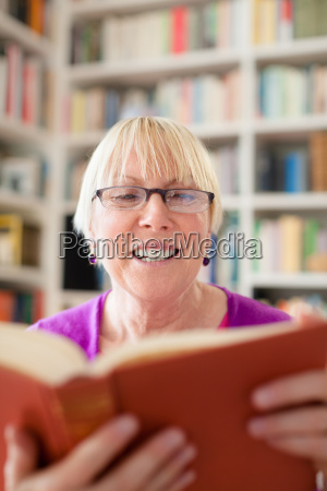happy senior woman with glasses reading